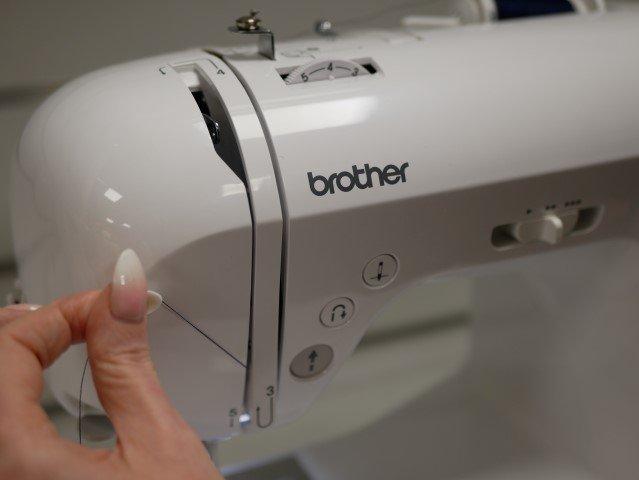 Guide thread through a sewing machine