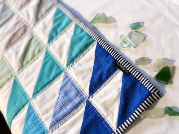 Beautiful mini quilt project using a charm pack and half square triangles