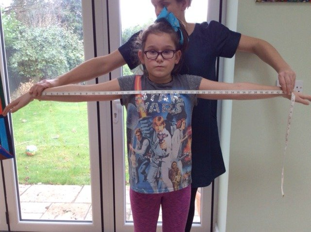 Measuring a child to sew them a top